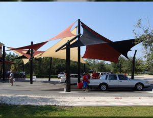 Tan, black, and red commercial sun shade panels for a parking lot