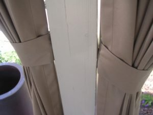 Sandy outdoor drapes bundled up