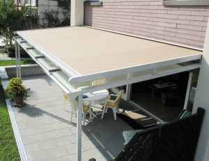 Tan awning fabric on a residential retractable awning with white beams