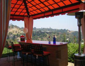 Custom cabana with red awning fabric over an outdoor bar