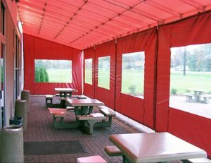 Red awning fabric on a commercial drop-roll awning
