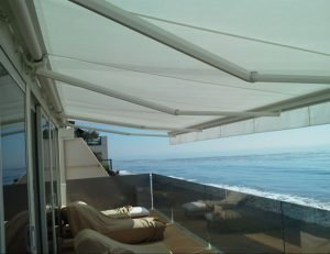 White awning fabric on a custom retractable awning overlooking the ocean