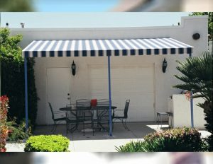 Residential patio shade awning with blue and white striped awning fabric