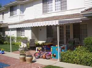 Residential patio shade awning with striped awning fabric