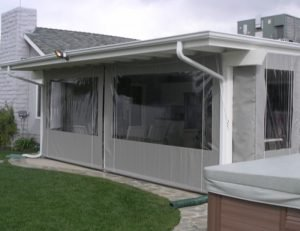 Drop-roll awning cover with clear plastic panels