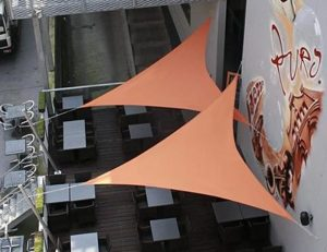 Light orange commercial sun shade panels for a patio