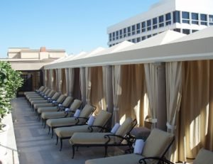 Commercial cabanas with tan awning fabric and drapes
