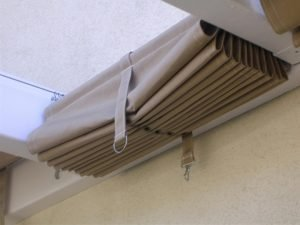 Retracted slide on wire awning with dark awning fabric