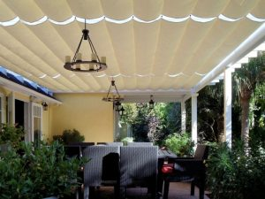 Residential slide on wire awning with white awning fabric and custom outdoor chandeliers