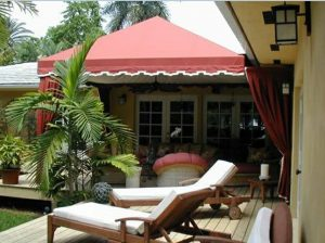 Residential patio shade awning with red and white awning fabric