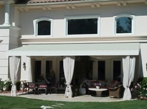 Residential patio shade awning with custom awning fabric and drapes