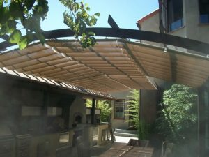 Residential trellis cover with tan slide on wire awning fabric