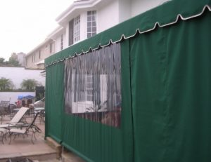 Drop-roll awning shade cover with green awning fabric