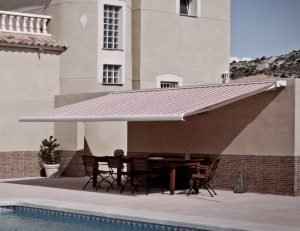 Residential retractable awning with red and white striped awning fabric