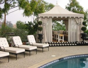 Custom pool cabana with beige awning fabric and custom drapes