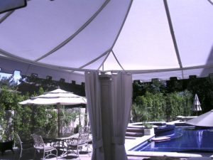 Custom awning with white drapes next to a pool