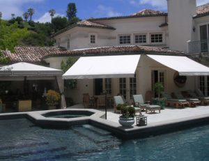 Retractable awnings with white awning fabric for a pool area