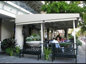 Beige storefront awning with white beams on a patio