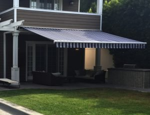 Custom residential retractable awning with blue and white awning fabric