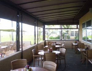 Commercial drop-roll awning shade for a patio area