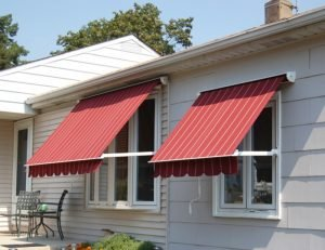 Residential retractable awnings on windows with red pinstriped awning fabric
