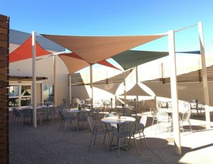 Tan, orange, and green commercial sun shade panels for an outdoor patio