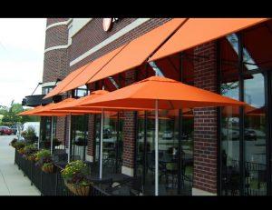 Orange commercial shade umbrellas and orange window awnings