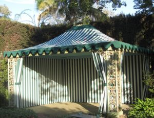 Residential cabana with striped green and white awning fabric
