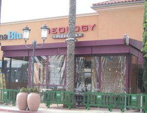 Maroon drop-roll awning shade with clear plastic covers
