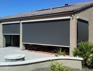 Residential drop-roll awning shade with dark awning fabric