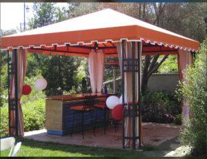 Residential cabana with orange awning fabric and custom drapes