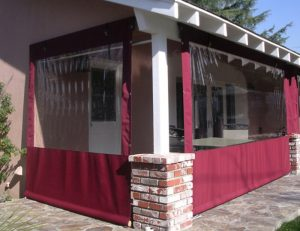 Drop-roll awning with clear plastic and red awning fabric