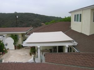 White residential trellis cover with beige awning fabric