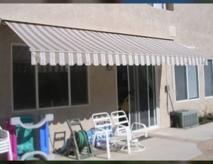 Patio retractable awning with grey and white striped awning fabric
