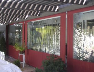 Red commercial drop-roll awning covers with clear plastic panels