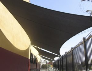 Dark sun shade sail panel on a patio