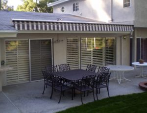Retractable awning for a home patio with striped awning fabric