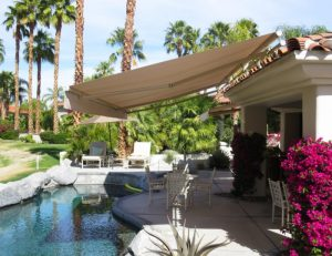 Tan retractable awning for a pool area