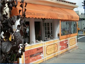 Custom orange storefront awning for Soleil French Bistro
