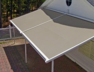 Residential retractable awning with dark tan awning fabric and white beams