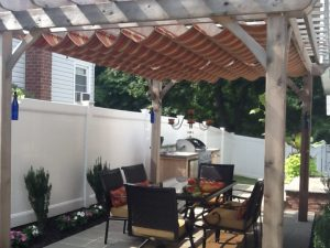 Wood trellis cover with red and gold slide on wire awning fabric