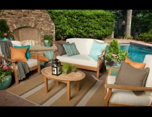 White, turquoise, and grey pad cushions for patio furniture in a pool area