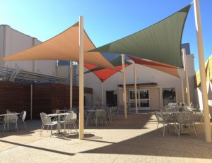 Olive green, tan, and orange sun shade panels for a patio
