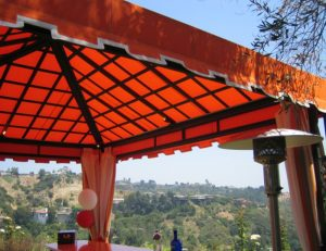 Residential cabana with orange awning fabric over an outdoor bar