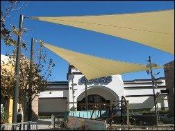 Tan sun shade sail panels outside of Sears