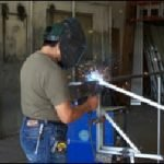 Welding a custom aluminum awning at our shop