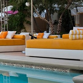 Custom pad cushions with yellow fabric next to a pool