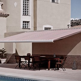 Striped retractable awning next to a pool