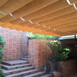 Outdoor retractable awning with tan fabric