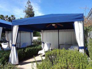 Custom cabana with blue awning fabric and white custom blinds